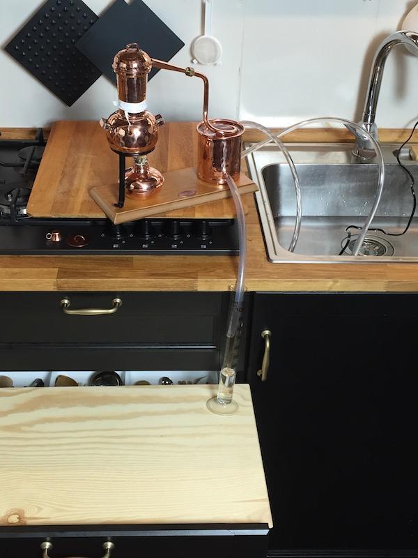 Mit offener Schublade und Holzbrett zum Auffangen des Destillates