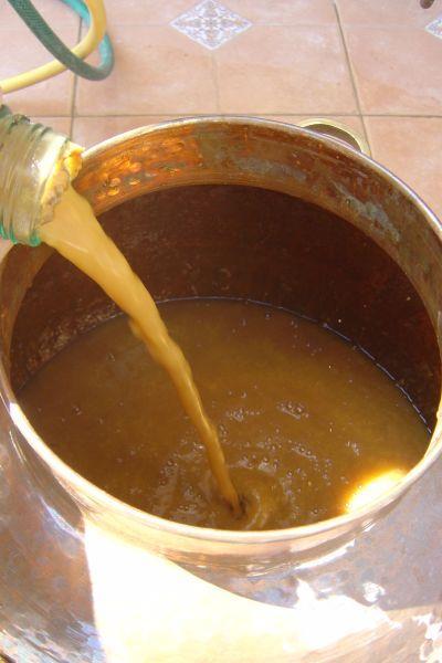 Einfüllen von Aprikosenmaische in einen Brennkessel aus Kupfer beim Schnapsbrennen